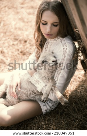 beautiful young blond woman with a lamb in the countryside