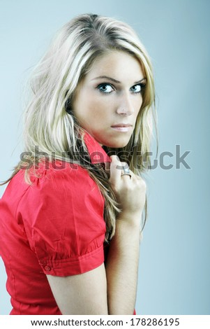 Beautiful young blond woman with a suspicious angry look staring balefully at the camera over her shoulder with an intense expression - stock photo