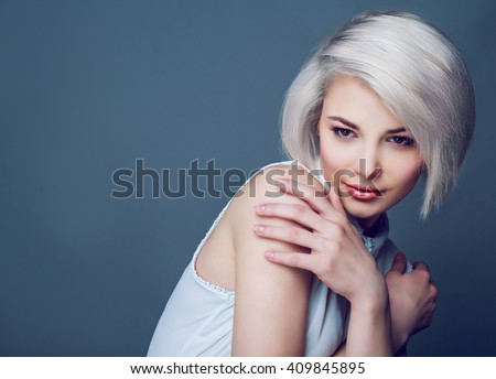 beautiful young blond woman with brown eyes against grey studio background - stock photo