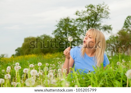 beautiful young blond woman with dandelion - stock photo