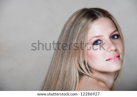 beautiful young blond woman with long hair looking into the camera in her early 20s