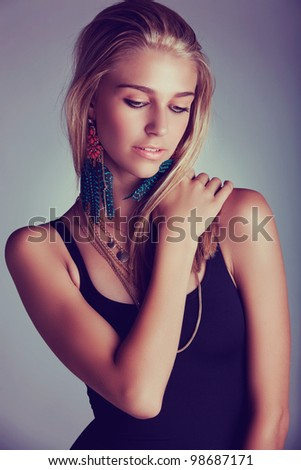beautiful young blond woman with long hair wearing long feather coral earrings - shot as low key portrait with retro effect. - stock photo