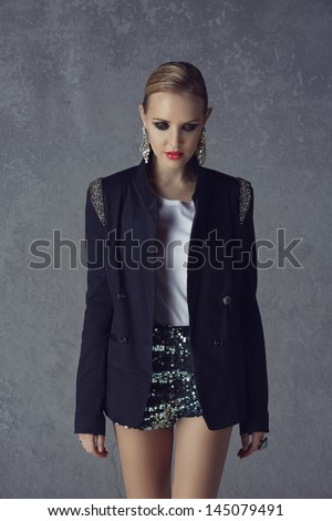 beautiful young blond woman with messy hair in a black blazer and sequin green shorts on grunge studio background - stock photo