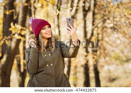 Beautiful young blonde Caucasian woman in jacket and modern knitted beanie hat taking a selfie on smart phone in autumn in park. Millennial teenage girl photographing herself outdoors in fall.