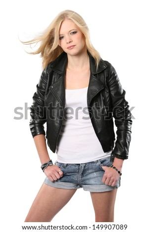 Beautiful young blonde fashion model wearing a leather jacket with wind in her hair - stock photo