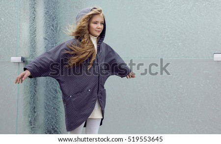 Beautiful young blonde girl in a coat and boots posing for fashion, children's clothing