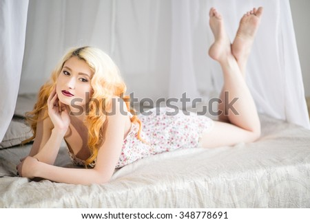 Beautiful young blonde girl in beautiful underwear lying on a bed in a light bedroom, glamor, sensuality, tenderness, beauty - stock photo