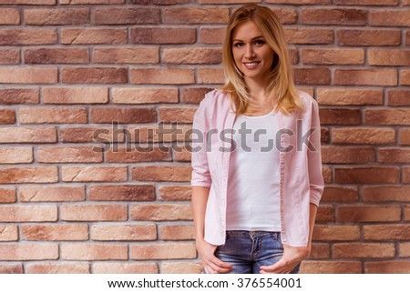 Beautiful young blonde girl in casual clothes posing, smiling and looking in camera, standing against brick wall