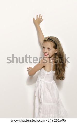Beautiful young blonde girl in white dress smiling and playing. Kid enjoying life and having fun - stock photo