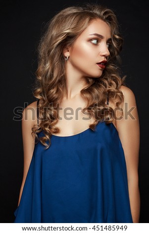 Beautiful young blonde girl looking to the side. Girl with professional make-up and hair styling - stock photo