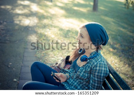 beautiful young blonde hipster woman on the phone in park on the bench - stock photo