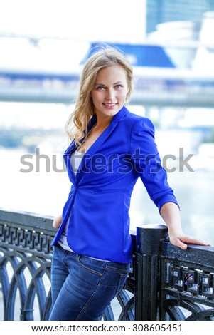 Beautiful young blonde in a blue jacket, portrait outdoors - stock photo