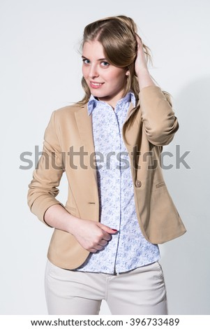 Beautiful young blonde in a light beige jacket. Fashion girl on a light background