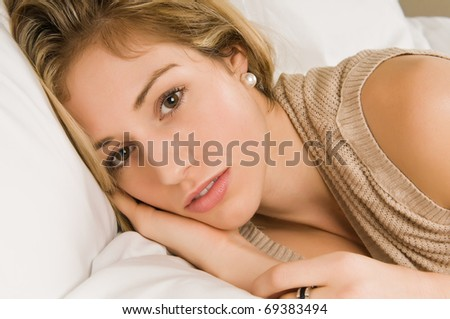 Beautiful young blonde in bed in a tan knit blouse - stock photo