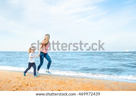 Beautiful young blonde mother and little cute girl run and laugh at the beach. Travel and Vacations.