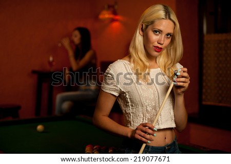 Beautiful young blonde playing billiard in a bar - stock photo