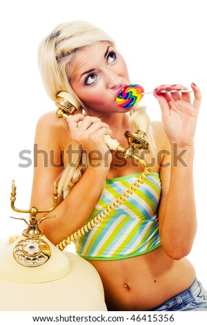 Beautiful young blonde posing with a lollipop and a vintage telephone