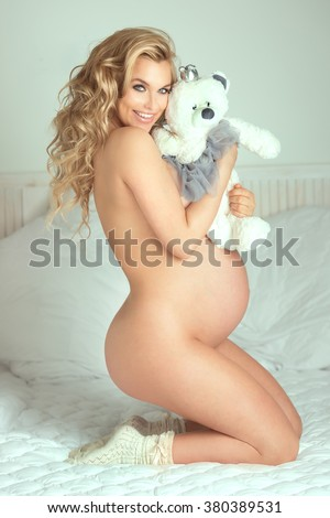 Beautiful young blonde pregnant woman naked, looking at camera. Smiling happy girl. - stock photo