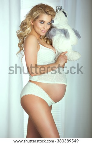 Beautiful young blonde pregnant woman posing in lingerie, looking at camera. Smiling happy girl. - stock photo