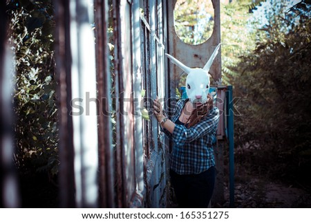 beautiful young blonde rabbit mask woman in an abandoned urban landscape - stock photo