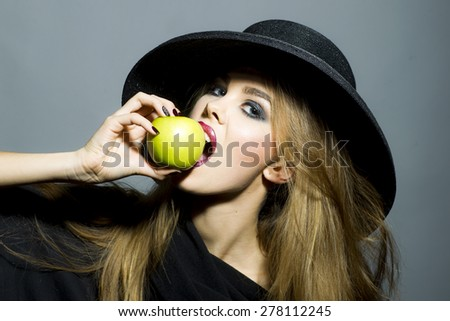 Beautiful young blonde sexy girl in retro black hat with bright make up biting fresh green apple standing on gray background copyspace, horizontal picture - stock photo