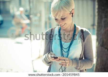 beautiful young blonde short hair hipster woman listening music earphones in the city - stock photo