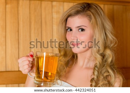 beautiful young blonde with a glass of beer in the sauna - stock photo