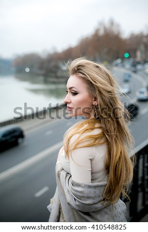 Beautiful young blonde with a perfect figure and long hair stands and looks thoughtfully at the road - stock photo