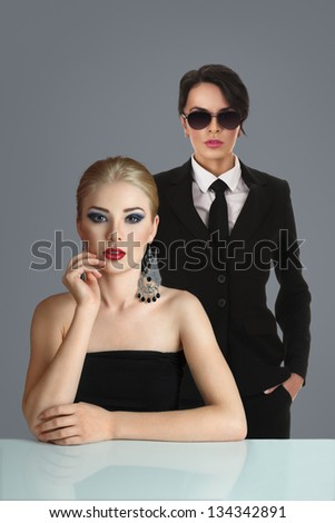 Beautiful young blonde woman and her lawyer behind shoulders - stock photo