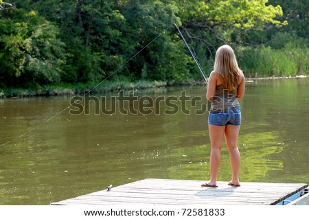 Beautiful young blonde woman, back to camera, fishing from dock or pier into a river - stock photo
