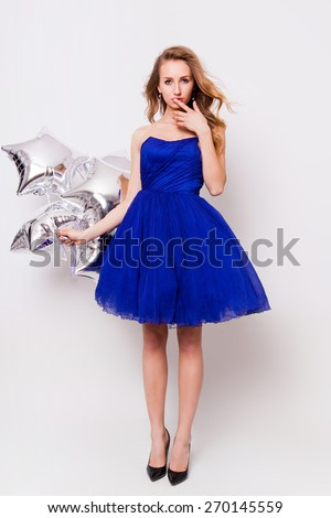 Beautiful young blonde woman celebrate prom and holding  silver party balloons. Wearing blue evening elegant dress and have day of. - stock photo