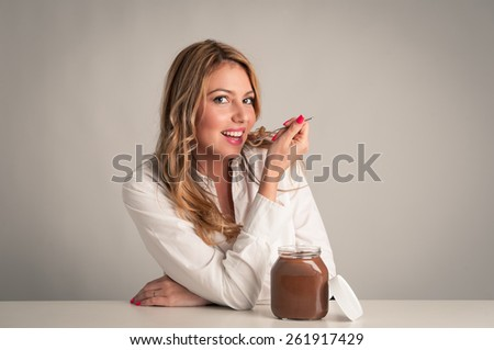 Beautiful young blonde woman eating chocolate cream with teaspoon. - stock photo