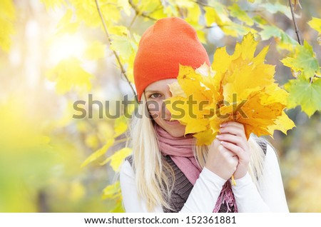 Beautiful young blonde woman flirting with yellow autumn leaves. - stock photo