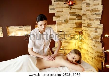Beautiful young blonde woman getting spa massage - stock photo