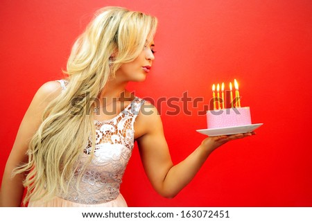 Beautiful young blonde woman holding a pink birthday cake. - stock photo