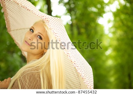 Beautiful young blonde woman holding umbrella with a dreamy faraway look in her eyes. - stock photo