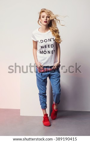 beautiful young blonde woman in a t-shirt red sneakers and jeans posing in studio. Fashion photo - stock photo