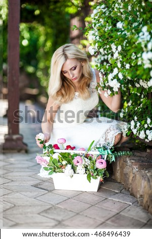 Beautiful young blonde woman in a white dress, bent over the basket of flowers on the street.