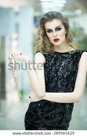 Beautiful young blonde woman in back dress in sequins with gold chin standing on store background, vertical picture - stock photo