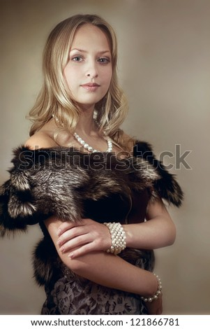 Beautiful young blonde woman in fur and pear beads - stock photo