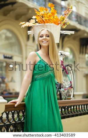 Beautiful young blonde woman in green dress, indoor