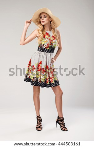 beautiful young blonde woman in nice spring dress and a hat posing in a studio. Fashion spring summer photo - stock photo