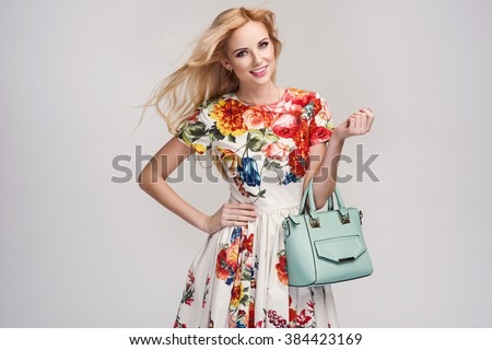 beautiful young blonde woman in nice spring dress, handbag posing in a studio. Fashion spring summer photo - stock photo