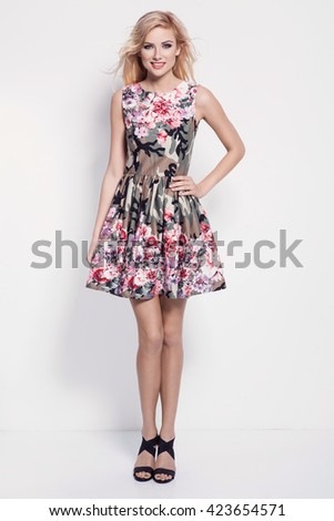 beautiful young blonde woman in nice spring dress, high heels shoes posing in a studio. Fashion spring summer photo
