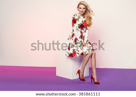 beautiful young blonde woman in nice spring dress posing in a studio. Fashion photo, high heel shoes - stock photo