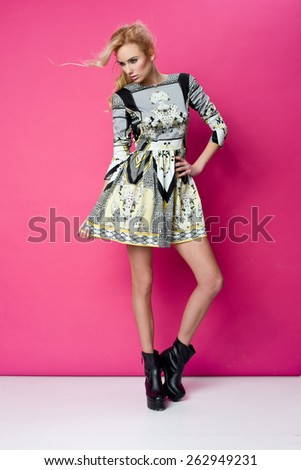 beautiful young blonde woman in nice spring dress, posing in studio. Fashion photo, blak boots - stock photo