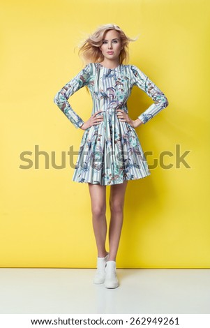 beautiful young blonde woman in nice spring dress, posing on yellow background in studio. Fashion photo, white boots - stock photo