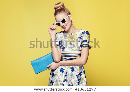 beautiful young blonde woman in nice spring dress, posing on yellow background in studio. Fashion photo, blue handbag and white sunglasses - stock photo