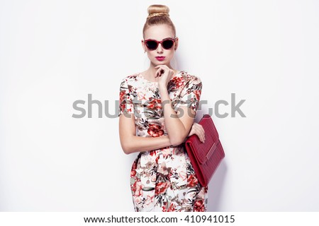 beautiful young blonde woman in nice spring dress, sunglasses, purse posing on white background in a studio. Fashion photo - stock photo