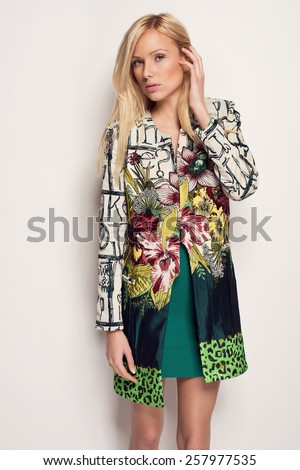 beautiful young blonde woman in nice spring flower pattern coat, posing in studio. Fashion photo - stock photo